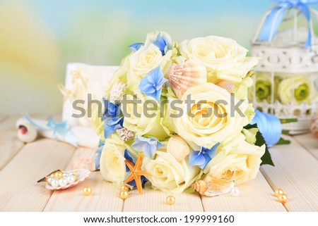 Beautiful wedding bouquet with roses on wooden table, on nature background
