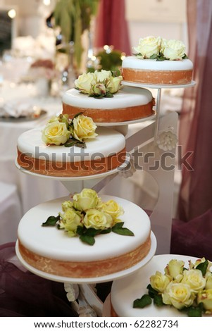 Beautiful wedding cake decorated with yellow roses - stock photo