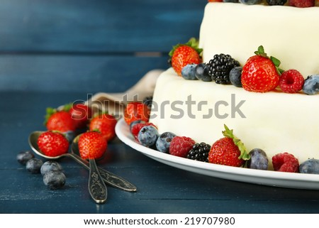Beautiful wedding cake with berries on  dark wooden background - stock photo