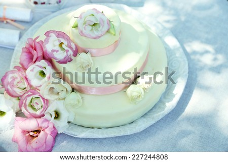 Beautiful wedding cake with flowers on table, outdoors - stock photo
