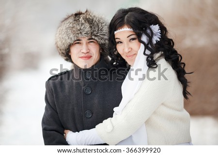 Beautiful wedding couple, asian bride and groom embraced. Young man in winter coat and fur hat, bride in white wedding dress with sheepskin and veil. Cold season warm clothing. Close-up portrait. - stock photo