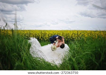 beautiful wedding couple at the field of yellow flowers - stock photo