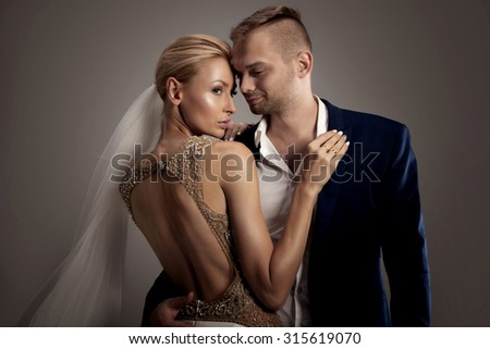 Beautiful wedding couple. Blonde woman in white dress and handsome man in suit. Love content. - stock photo