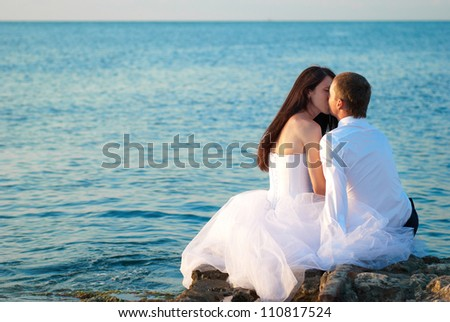 Beautiful wedding couple- bride and groom kissing at the beach. Just married - stock photo