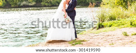 Beautiful Wedding couple holding hands and hugging - stock photo