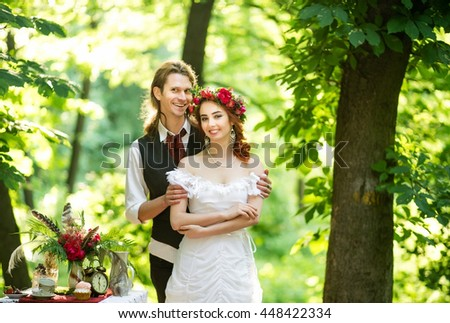 Beautiful wedding couple in the boho style, bride and groom walking in a summer park