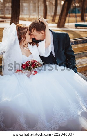 Beautiful wedding couple is enjoying wedding. Groom and Bride in a park. wedding dress. Bridal wedding bouquet of flowers. Wedding shot of bride and groom in park