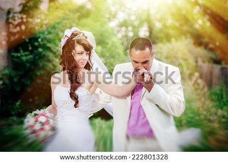 Beautiful wedding couple is enjoying wedding. Groom and Bride in a park. wedding dress. Bridal wedding bouquet of flowers. Wedding shot of bride and groom in park - stock photo