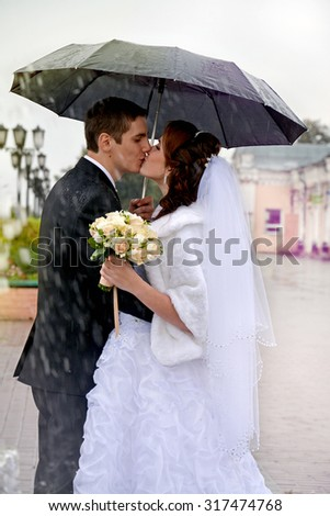 Beautiful wedding couple kissing in the rain. Bride and groom walking on the street under an umbrella on a rainy day