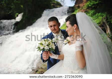 beautiful wedding couple near waterfall - stock photo
