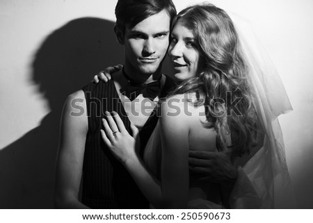 Beautiful wedding couple standing beside on white wall background. Hug each other. Black and white portrait
