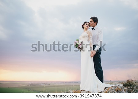 Beautiful wedding couple with bouquet flowers on the sunset