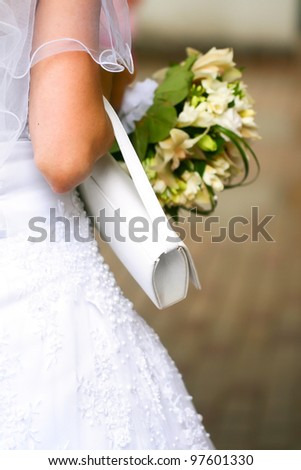 Beautiful wedding dress on a bride with veil, white handbag and beautiful bouquet in hands. - stock photo