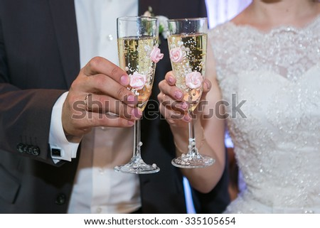 Beautiful wedding glasses with sparkling wine and flowers - stock photo