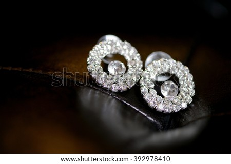 Beautiful wedding jewel for bride and groom. Beauty of wedding accessories indoors. Close-up bridal details of marriage. Female and male decoration for couple. Jewelry for man and woman - stock photo