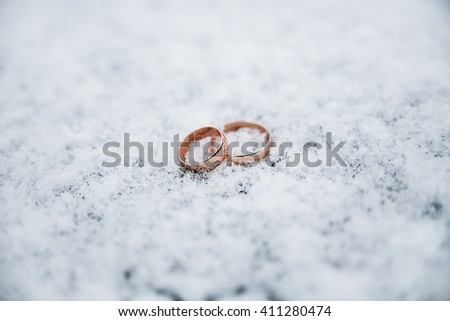 Beautiful Wedding rings on the snow. Soft focus