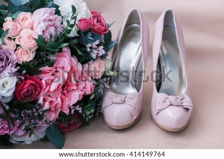 Beautiful wedding shoes with high heels and a bouquet of colorful flowers hydrangea, peonies and roses on a background of kraft paper, decorations, preparing for the wedding, details, boudoir