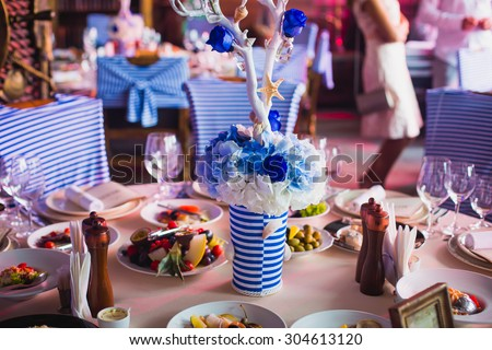 Beautiful wedding table and interior decoration with flowers in blue colors - stock photo
