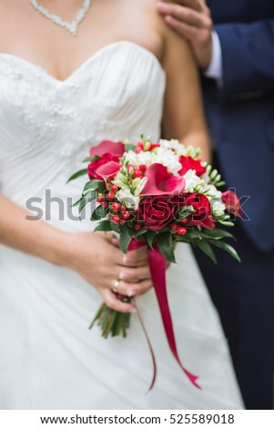 Beautiful Weding bouquet of different flowers in the hands of the bride in a white wedding dress. Bride holding grooms hand. Wedding ceremony concept