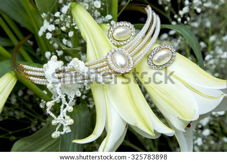 beautiful weeding jewellery placed on white and yellow tubular Lilly flowers - stock photo