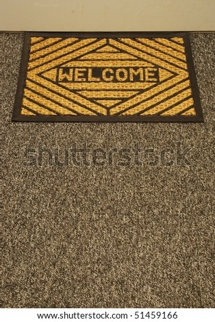 beautiful welcome home door mat on a grey carpet - stock photo