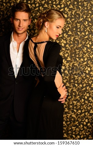 Beautiful well-dressed couple standing against abstract wall - stock photo