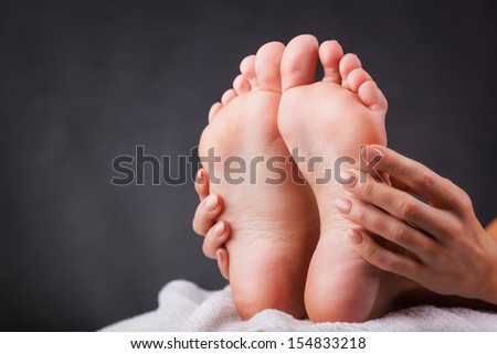 Beautiful well-groomed female a foot and a heel on a black background - stock photo
