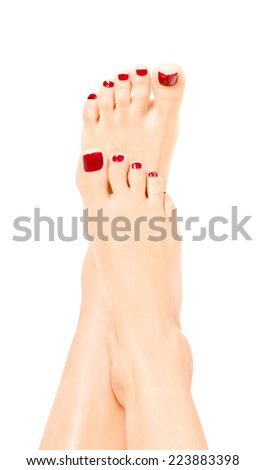 Beautiful well-groomed female feet with red pedicure - stock photo