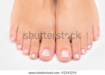 Beautiful well-groomed female feet with the French pedicure - stock photo