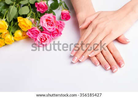 Beautiful well-groomed female hands. French manicure with pink  and yellow roses on a white background.