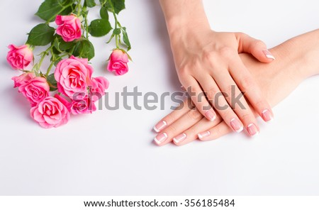 Beautiful well-groomed female hands. French manicure with pink roses on a white background.