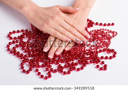 Beautiful well-groomed female hands on red beads. Festive manicure. French moon manicure on red beads. - stock photo