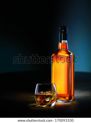Beautiful Whisky Bottle and Glass shot in Dimly lit room - stock photo
