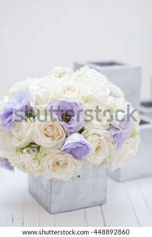 Beautiful white and blue flowers in silver vase.White background