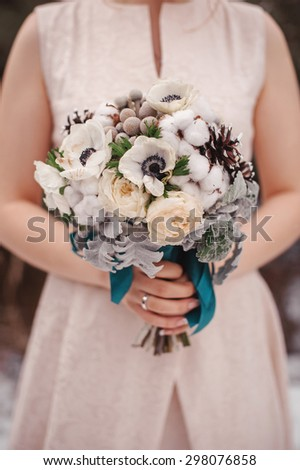 beautiful white and brown winter wedding bouquet in bride's hands - stock photo