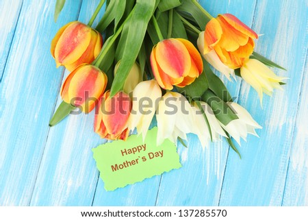 Beautiful white and orange tulips on color wooden background