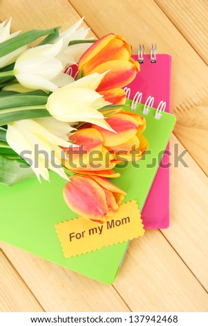 Beautiful white and orange tulips on wooden background