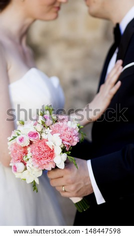 Beautiful white and pink wedding bouquet with bride and groom in the background - stock photo