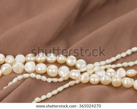 beautiful white beads made from freshwater pearls on brown fabric with pleats
