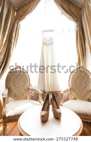Beautiful white bridal shoes and dress at luxurious bedroom - stock photo