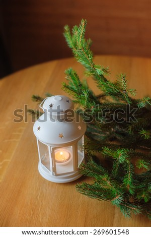 Beautiful white candlestick in the form of a small house and a sprig of Christmas tree on a wooden table. - stock photo