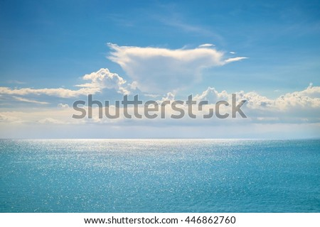 Beautiful white clouds on blue sky and calm ocean with sunlight reflection, Bali. Sunny sky with fantastic clouds and blue ocean. Calm sunny ocean and sky. Amazing turquoise ocean. Tranquil Bali ocean - stock photo