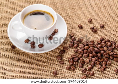 Beautiful white coffee cup and saucer and coffee beans on the background of burlap. Dark background. - stock photo