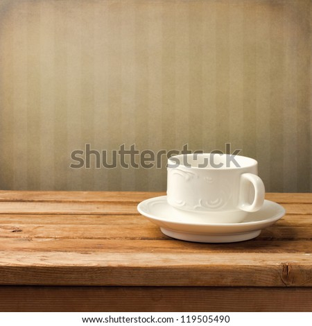 Beautiful white coffee cup over vintage background - stock photo