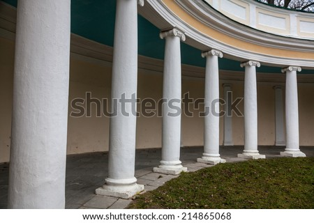 Beautiful white colonnade at autumn park