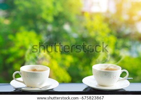 Beautiful white cups of coffee with smoke , nature background and warm light