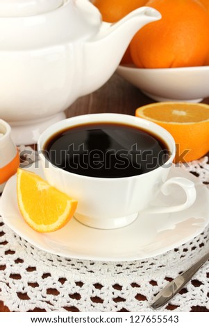 Beautiful white dinner service with oranges on wooden table close-up