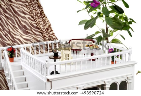 Beautiful white doll's house with furniture on textile