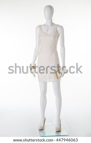 Beautiful white dress and beige high-heeled shoes. Showcase of stylish boutique. Female mannequin in a dress with accessories.