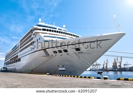 beautiful white giant cruise ship on stay at harbor, blue cloudy sky in background and visible lens flare - stock photo